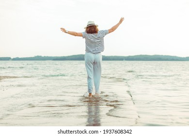 woman in white clothes walking by sea beach summer time