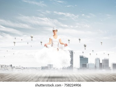 Woman in white clothing keeping eyes closed and looking concentrated while meditating on cloud with cityscape view and flying balloons on background.