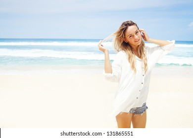 woman in white clothing refreshing at the ocean, bali