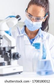 Frauen in weißem Mantel, Schutzbrille und Gesichtsmaske sehen das Reagenzglas in einer Hand an und halten eine Objektscheibe in der anderen Hand. Coronavirus COVID-19 Konzept.