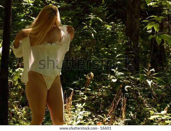 Woman in white corset taking off shirt.