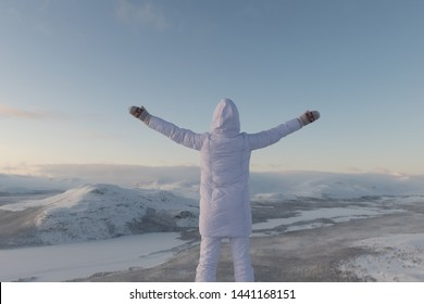 Woman in white costume posing on scenic arctic background
