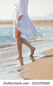 woman in white cotton dress walking on sandy beach sunny summer day lower body side view