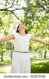 Woman in white dress with arms outstretched while standing in park