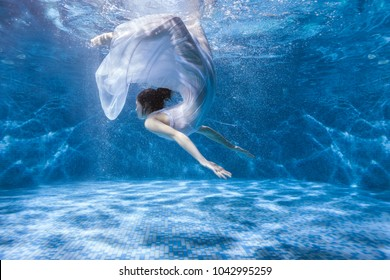 Woman in a white dress dives under the water in the pool.