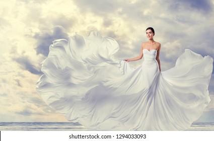 Weiße Kleidung, Modemodell auf Long-Silk-Fluttering-Gown, Flügeltuch auf Wind auf Sky-Wolken-Hintergrund