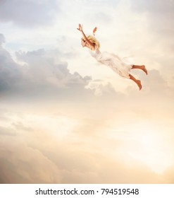Woman in a white dress flying in the sky. Serenity