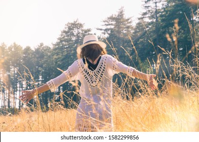 Woman in white dress and hat walking in meadow with hands outstretched on sunny summer day.