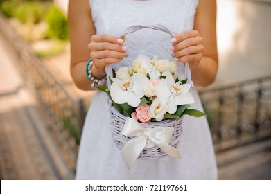 Woman in white dress holding a little wicker basket of flowers no face close up