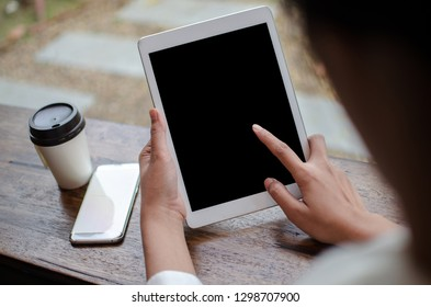 woman in white dress holding tablet in cafe