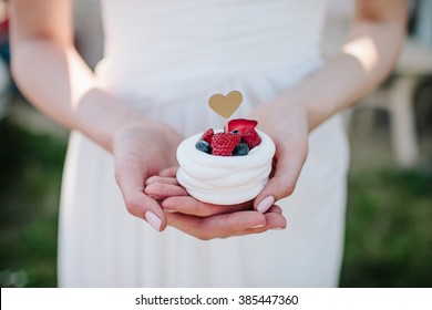 Woman in white dress holds cake with berries and heart sign