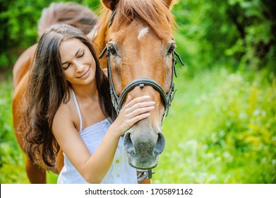 Woman in white dress keeps brown horse against background of summer green park.