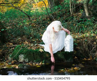woman with white dress and a lantern at a forest brook shore