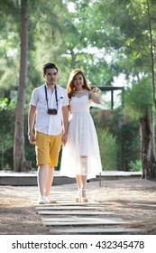 The woman in white dress and man in white shirt, yellow shorts are walking