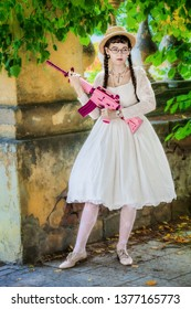 Woman in a white dress with a pink rifle plays airsoft in an abandoned building.