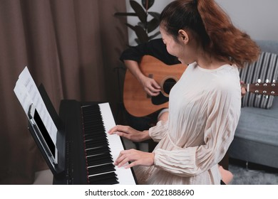 A woman in white dress playing paino with happyness with his friend who playing guitar. Musician practicing paino.
