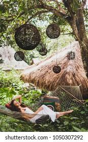 Woman in white dress relaxing in hanging hammock in bali garden. Round wooden wicker lantern hanging on tree