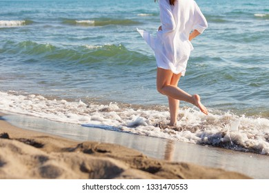 woman in white dress run  through the water on sandy sea beach sunny summer day lower body