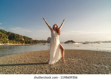 Woman in white dress at the sea on the sunset on Palawan island, Philippines