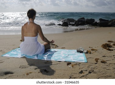 Woman in white dress sitting on beach towel relaxing, facing the ocean