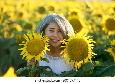 Woman in white dress standing in a field of sunflowers in summer bloom. Dixon, Solano County, California.