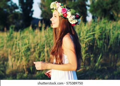 Woman in white dress standing in field wearing flower crown. Young forest inspired bride, bohemian girl, photo toned style instagram filters.