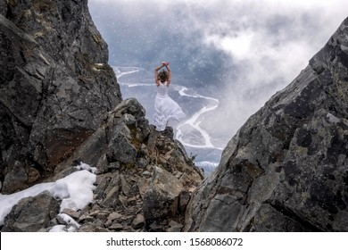 Woman in white dress standing on the edge  of a steep rock with a river view in clouds in a snow storm. First snow storm in North Cascades National Park. Concrete. Washington State. USA
