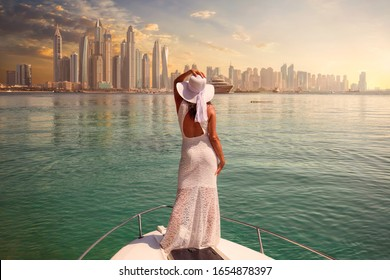 Woman in a white dress is standing on a boat looking to the skyline of Dubai Marina - Shutterstock ID 1654878397