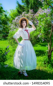 Woman in a white dress and straw hat walks in the park in spring.