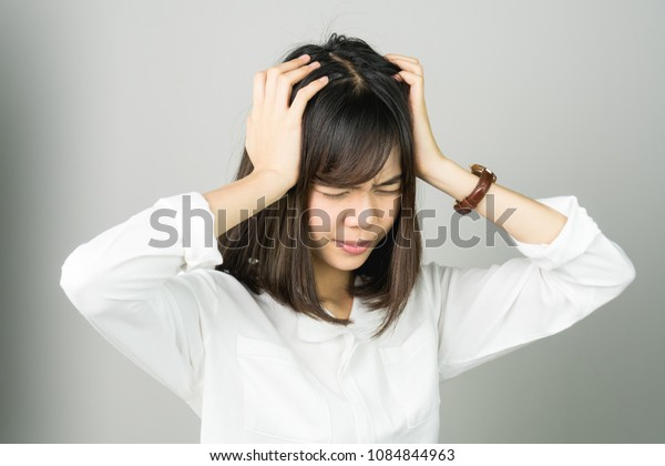 Woman in a white dress is touching head to show her headache. Causes may be caused by stress or migraine. Or because too much work. The concept of stress from hard work is bad for health.
