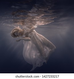 Woman in a white dress under water