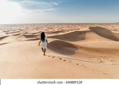 Woman with white dress walking in the Dubai desert sand dunes with footsteps in the  desert sand,, young woman walking golden sand on a bright summer day, Dubai Emirates holliday vacation concept