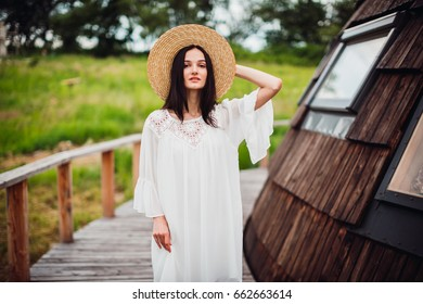 Woman in white dress walks on the wooden path