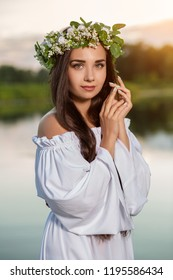 Woman in white dress in the water. Art Woman with wreath on her head in river. Wreath on her head, Slavic traditions and paganism