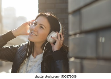 Woman with white earphones listen music in city