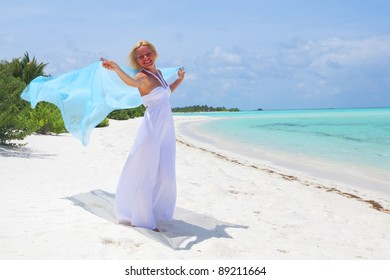woman with a white fabric in his hands on the beach