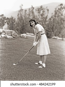 Woman in white gloves playing golf
