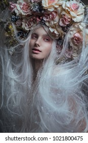 Woman with white hair and white roses and snow on face