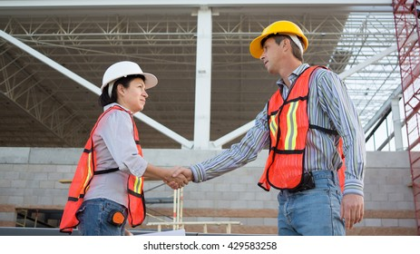 A woman in a white hardhat and safety gear shakes hands with a male in a yellow hardhat on an industrial construction job site.