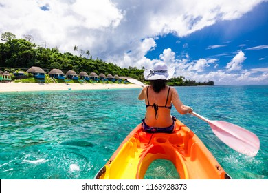 Woman in white hat Kayaking in the lagoon of tropical Samoa Islands