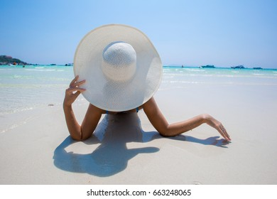 Woman in white hat lying on the seashore in water, blue sea and sky background