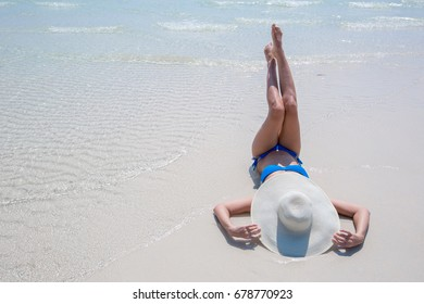 Woman in white hat lying on the beach, blue sea and sky background