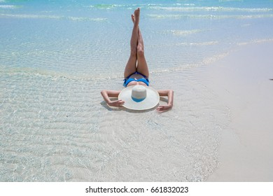 Woman in white hat lying in water on the beach, blue sea and sky background