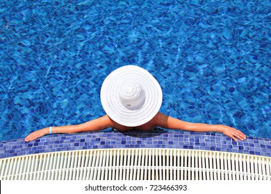 Woman in a white hat on the bllue pool background, relaxing in the water, shallow focus