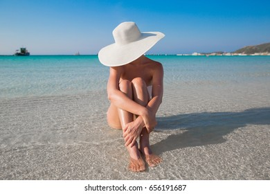 Woman in white hat sitting on the seashore in water, blue sea and sky background
