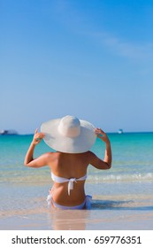 Woman in white hat sitting on the seashore in water, blue sea background