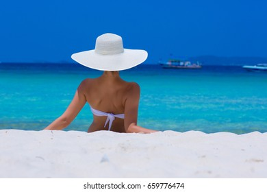 Woman in white hat sitting on the beach, blue sea and sky background