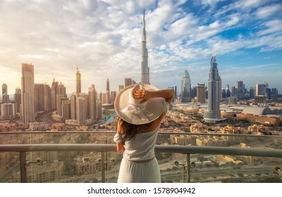 Woman with a white hat is standing on a balcony in front of the skyline from Dubai Downtown - Shutterstock ID 1578904942