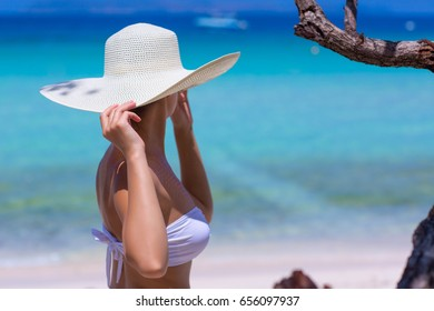 Woman in white hat standing on the beach, blue sea and sky background