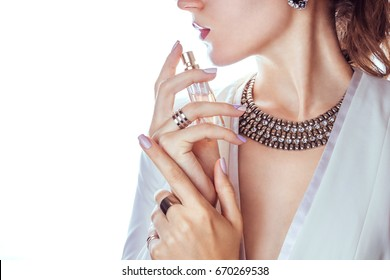 Woman in white jacket applying perfume on her neck